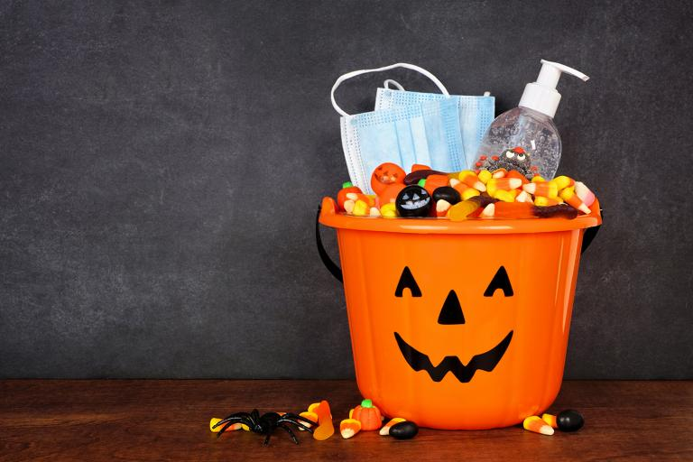 a trick or treat pail with sanitizer and a mask